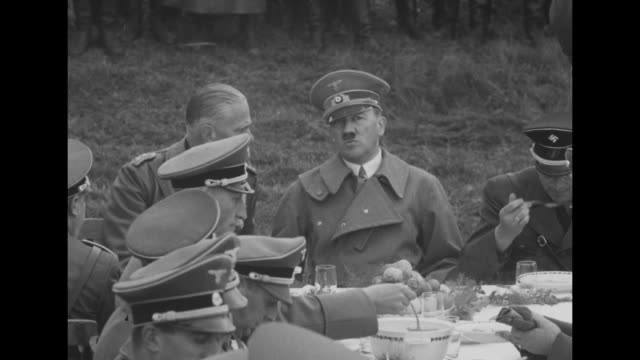 nazi officials sitting outdoors at table in field eating lunch soldiers standing in formation in background between franzensbad and eger / closer... - field marshal stock videos and b-roll footage