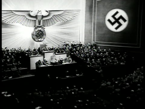 vídeos de stock e filmes b-roll de nazi swastika eagle symbol reichstag int ha ws nazi meeting in hall ms adolf hitler standing for recognition ext ha ws hitler w/ officials looking at... - 1939