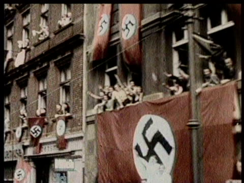 vídeos de stock, filmes e b-roll de nazi tanks, soldiers, and officers roll into czechoslovakia after conquering the nation / czech citizens salute the troops from the sidewalks /... - adolf hitler