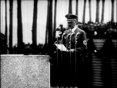 nazi troops marching at nuremberg / adolf hitler approaching microphone and giving speech / nazi flags and building with swastika on it / nazi troops... - 1937 stock-videos und b-roll-filmmaterial