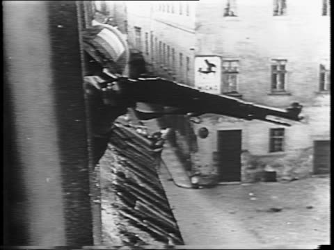 nazi troops police streets / crowd in street runs from nazi soldiers / hand grenade case opens and grenades are removed / a man loads gun / sniper... - prague stock videos & royalty-free footage