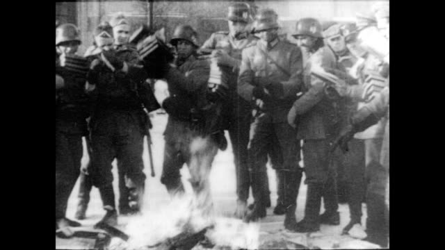 / Nazis and German soldiers throwing books into a fire that is burning in the middle of the street / Nazis stand around the fire and watch / Nazis...