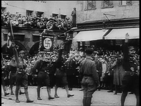 Nazis giving fascist salute marching with flags at Nuremberg rally / newsreel