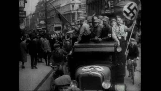 nazis marching down streets celebrating and waving flags - hakenkreuz stock-videos und b-roll-filmmaterial