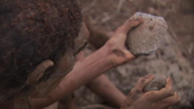 stockvideo's en b-roll-footage met a neanderthal pounds rocks to make tools. - prehistorische mens
