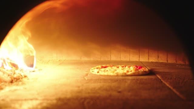 neapolitanische pizza aus holzofen mit einer schale genommen - italian culture stock-videos und b-roll-filmmaterial
