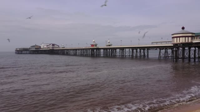 near deserted beach, promenade and pier as people heed the official advice and stay home on easter sunday, traditionally a busy weekend for day... - pier stock videos & royalty-free footage
