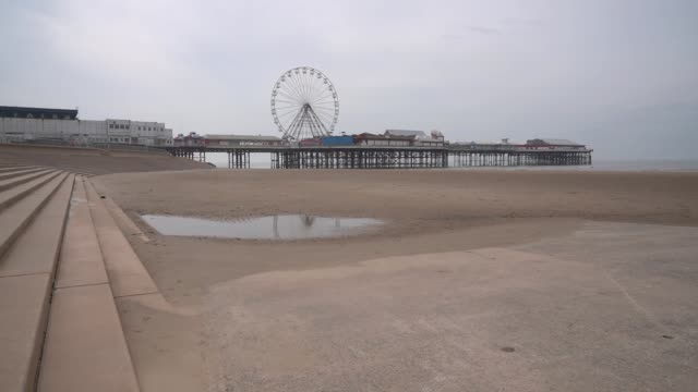 near deserted beach, promenade and pier as people heed the official advice and stay home on easter sunday, traditionally a busy weekend for day... - ブラックプール点の映像素材/bロール