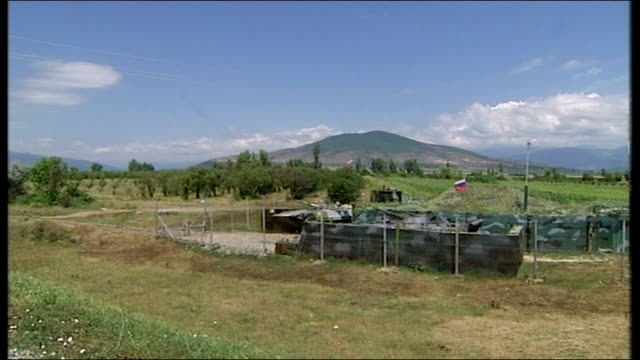 vídeos y material grabado en eventos de stock de views of countryside as smoke rises and sound of artillery heard sot view of fields, large hill on skyline, russian flags at roadside reporter to... - georgia