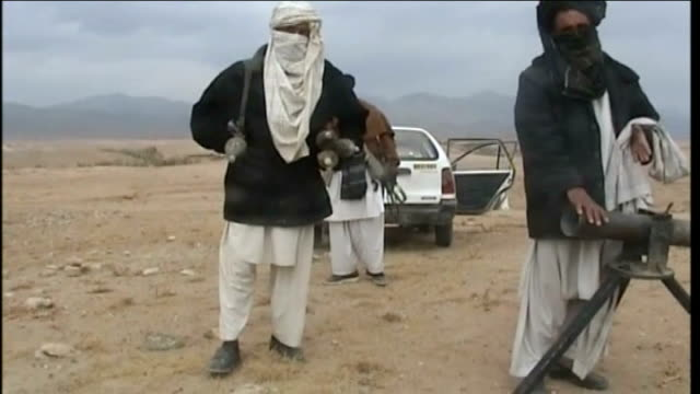 EXT Long shot Taliban fighters with motorbikes and other vehicle parked on dusty mound Armed Taliban militants crouched with weapons and arms Various...
