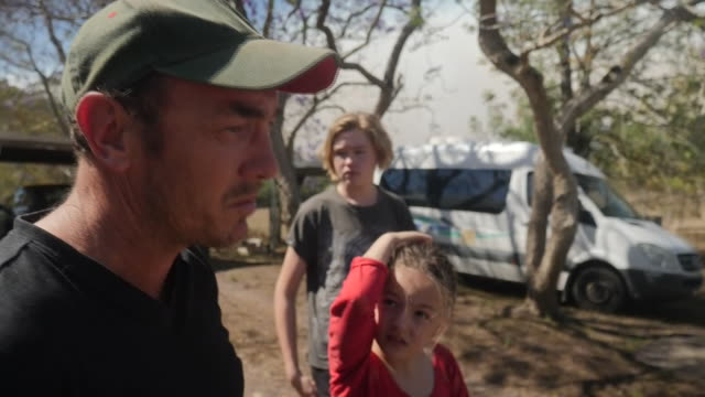 nearly 100 fires are raging across eastern australia shows family that have had to evacuate due to the wildfires people carrying belongings and... - forest fire stock videos & royalty-free footage