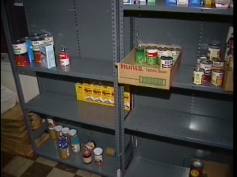nearly empty shelves are shown at the salvation army food bank around thanksgiving in boston. scattered about on the shelves are a few cans and boxes... - salvation army stock videos & royalty-free footage