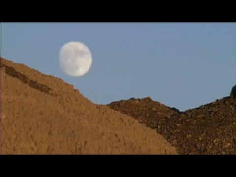 nearly full moon hanging low over horizon after just having risen over badlands of bisti/de-na-zin wilderness area / new mexico - 悪地地形点の映像素材/bロール