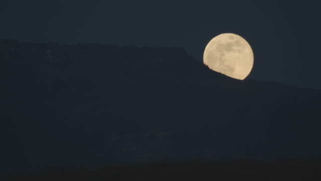 a nearly full moon rises over a mountain ridge in western colorado at night - full moon stock videos & royalty-free footage