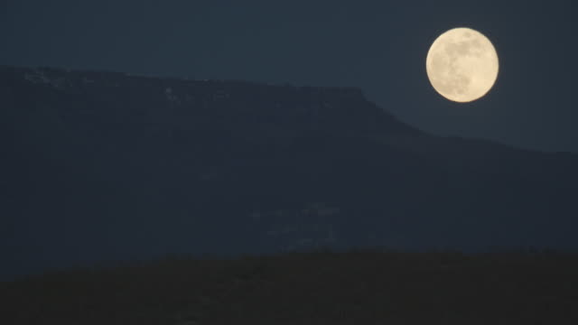a nearly full moon rises over the grand mesa overlooking grand junction, colorado - full moon stock videos & royalty-free footage