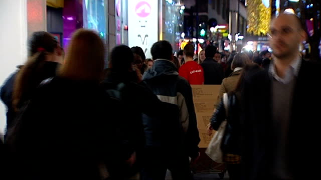 vídeos de stock, filmes e b-roll de nearly two million unemployed / woolworths to close all stores london oxford street shoppers along past shops and christmas lights shoppers along... - woolworths