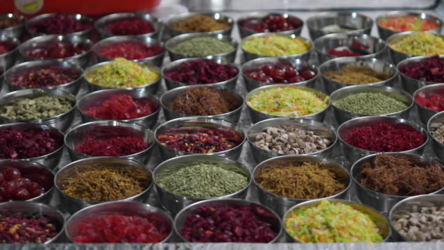 a neat display of various colourful ingredients for an indian paan at the stall of a street vendor - gewürz stock-videos und b-roll-filmmaterial