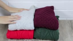 Neatly folded winter clothes. Folding sweaters in a pile. Cozy sweaters are lying in a pile. A female hand on stacks warm sweaters in pile. Female stacking the warm sweaters into the pile.