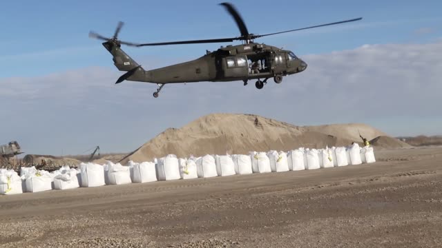nebraska national guard fill and rig up sandbags with slings and conduct vertical lift hook-up operations with uh-60 black hawk helicopters at the... - 緊急用具点の映像素材/bロール