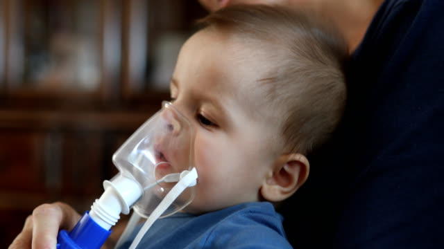 nebulizer treatment for sick infant baby - influenza virus video stock e b–roll