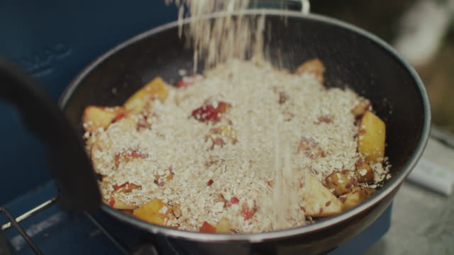 Nectarines, apples, bananas, oats, cinnamon in a frying pan on gas stove