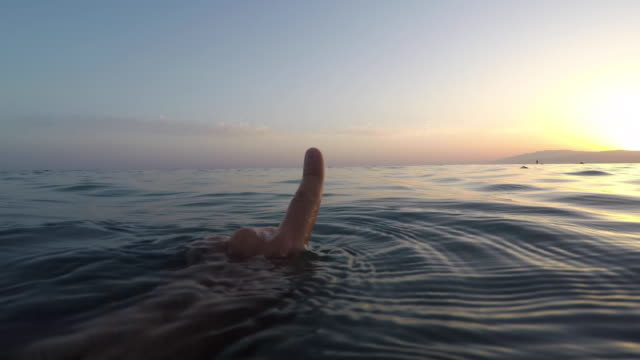 negative emotion. man doing a negative sing with his index finger while swimming in the sea. - deterioration stock videos & royalty-free footage