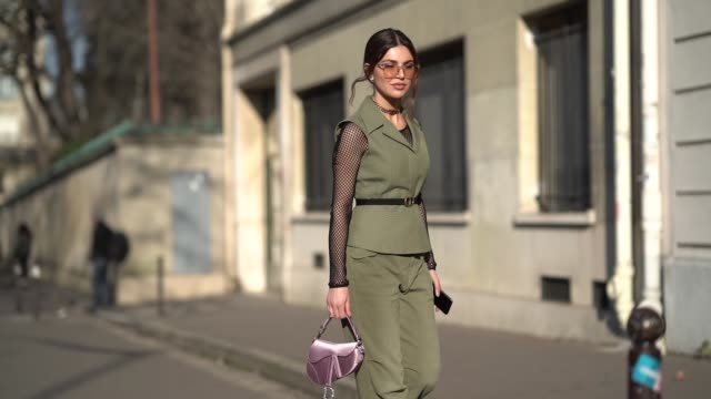 negin mirsalehi wears a green sleeveless jacket, a green pants, a pink dior saddle bag, sunglasses, outside dior, during paris fashion week - haute... - street style stock videos & royalty-free footage