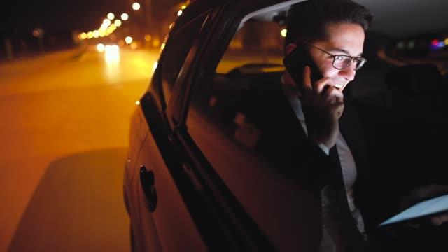 vidéos et rushes de des conversations d'affaires négociation sur s'asseoir arrière d'une voiture - siège arrière de passager