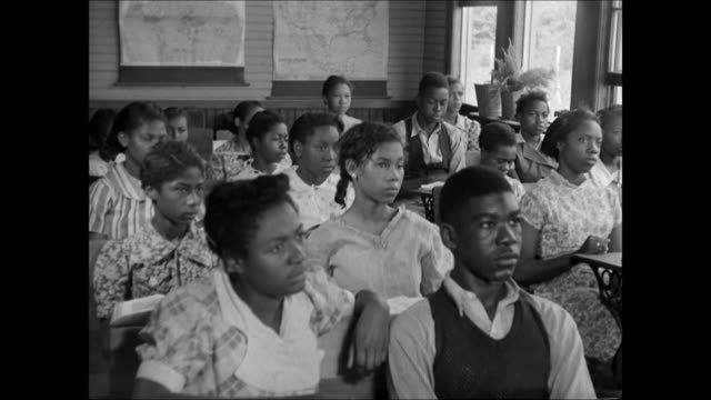 NegroAmericans at school school yard INT WS BlackAmerican students in class raising hand WS Teacher picking student student goes up to blackboard...