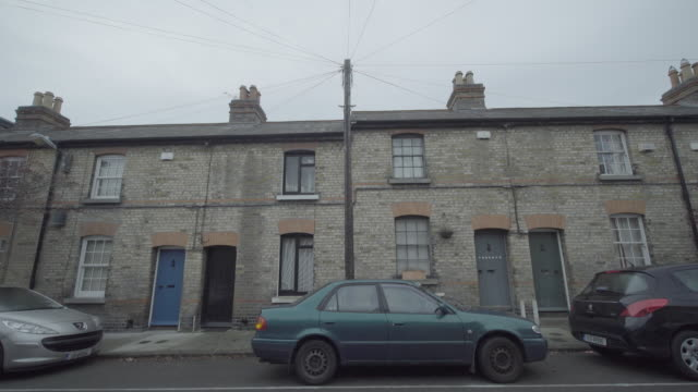 vidéos et rushes de ms, neighborhood houses and cars, tilt up to electrical lines, europe / ireland / dublin - quartier résidentiel