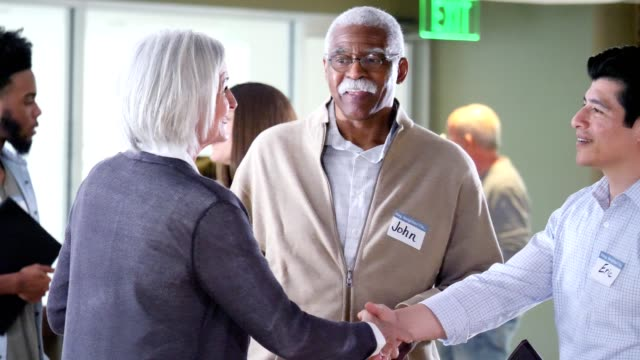 neighbors greet one another at community event - seminar stock videos & royalty-free footage