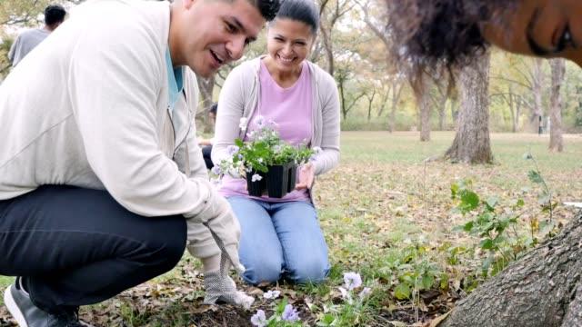 Neighbors plant flowers in their community