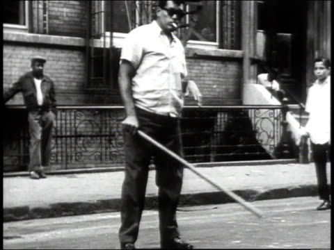 stockvideo's en b-roll-footage met 1965 pan neighbors playing stickball on a bronx street / new york city, new york, united states - 1965