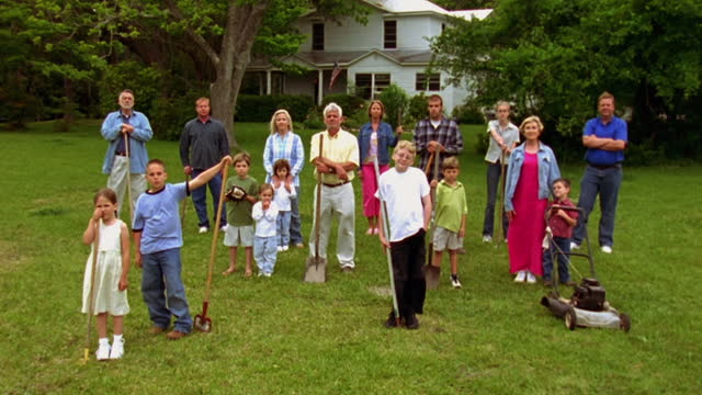 neighbors stand together in a backyard holding lawn tools. - nachbar stock-videos und b-roll-filmmaterial