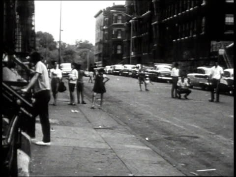 1965 PAN neighbors watching a stickball game on a Bronx street / New York City, New York, United States