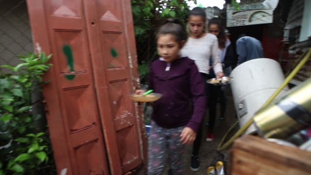 vidéos et rushes de neighbors with their children eat a plate of meal in a soup kitchen organized by barrios de pie social organization in dock sud neighborhood on... - buenos aires