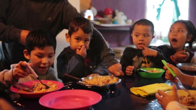 neighbors with their children eat a plate of meal in a soup kitchen organized by barrios de pie social organization in dock sud neighborhood on... - ブエノスアイレス点の映像素材/bロール
