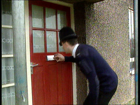 Neighbourhood Watch Patrols ITN Oxford EXT MS SIDE policeman looking through letter box on front door of house