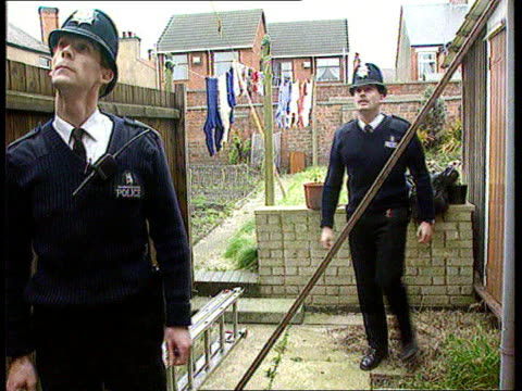 Neighbourhood Watch Patrols ITN Oxford EXT MS SIDE two policeman in back garden and looking up at house BV Policemen down front path to police van