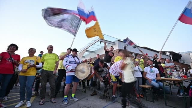neighbours and cycling fans set off smoke bombs and pop champagne bottles at a sports hall in the tiny slovenian town of komenda, north of capital... - tour de france stock-videos und b-roll-filmmaterial