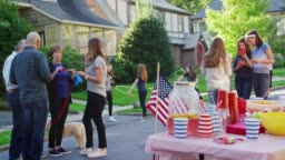 Neighbours talk, eat and play at a block party