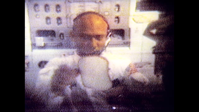 / neil armstrong and buzz aldrin floating around in zero gravity while listening to radio and news from houston mission control command / astronauts... - sala di controllo video stock e b–roll