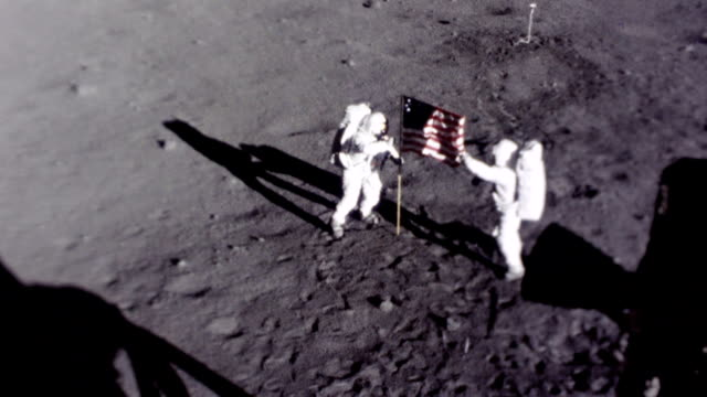 vídeos de stock e filmes b-roll de neil armstrong and buzz aldrin planting american flag on the moon surface during apollo 11 mission. neil armstrong and buzz aldrin planting us flag... - 1969