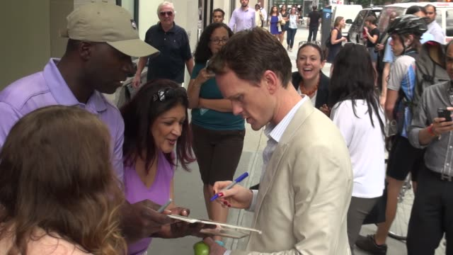 Neil Patrick Harris wearing red nail polish exits The Huffington Post signs for fans poses for photographers before leaving in Celebrity Sightings in...