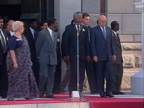 Nelson Mandela and F W De Klerk stand outside the South African parliament building following Mandela's appointment as President