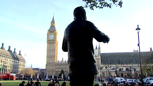 floral tributes and people around nelson mandela statue in westminster; framed photograph 'africa's father' and burning candles / 'nelson mandela'... - single rose stock videos & royalty-free footage