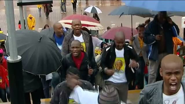 nelson mandela death public reaction to memorial south africa johannesburg soweto ext people along with umbrellas people towards up steps people... - soweto stock videos and b-roll footage