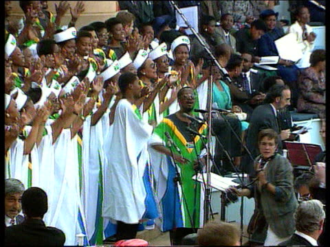 vídeos de stock, filmes e b-roll de pretoria ext lms choir singing at ceremony sot zoom in lms benazhir bhutto along towards lms us politician jesse jackson with chief gatsha buthelezi... - tomada de posse