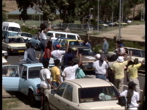 nelson mandela released from prison convoy of vehicles towards on road with motorcycle police escort convoy entering prison cameramen at scene - releasing stock videos and b-roll footage
