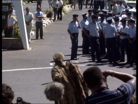 nelson mandela released from prison mandela supporter wearing fur robes and hat celebrating in road shouting at group of police officers dancing... - loslassen aktivitäten und sport stock-videos und b-roll-filmmaterial